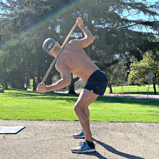 Athlete practices bentover torso rotations with pole, to improve spinal mobility.