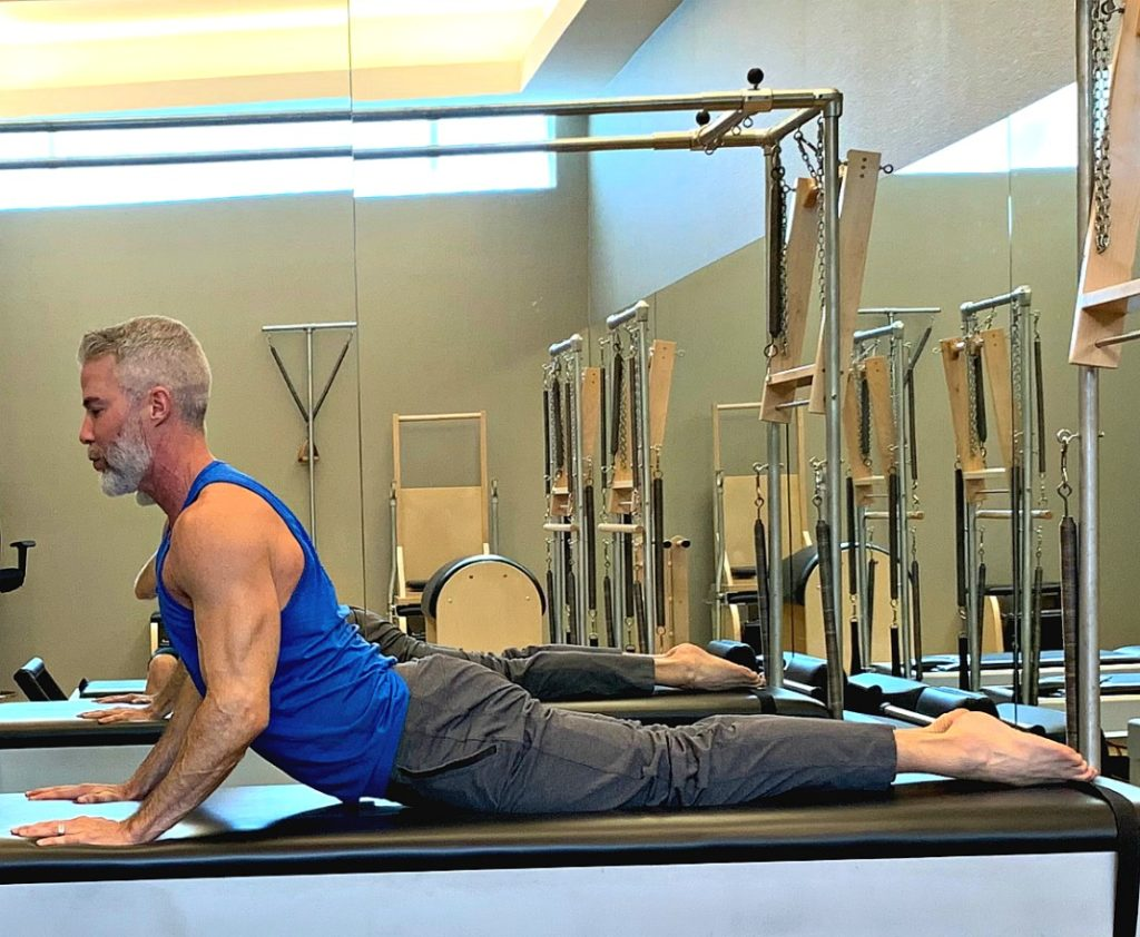 Dane enters pilates Swan exercise via Cobra stretch.