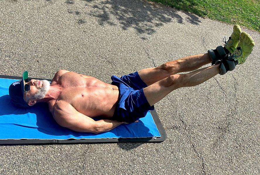 Mature athlete does abdominal conditioning exercises using ankle weights.