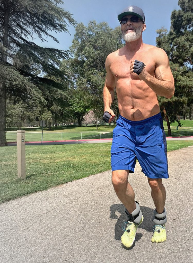Dane Findley, age 53, does exercises with ankle weights outdoors.