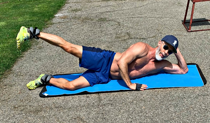 Older, fit man exercising in park using ankle weights.