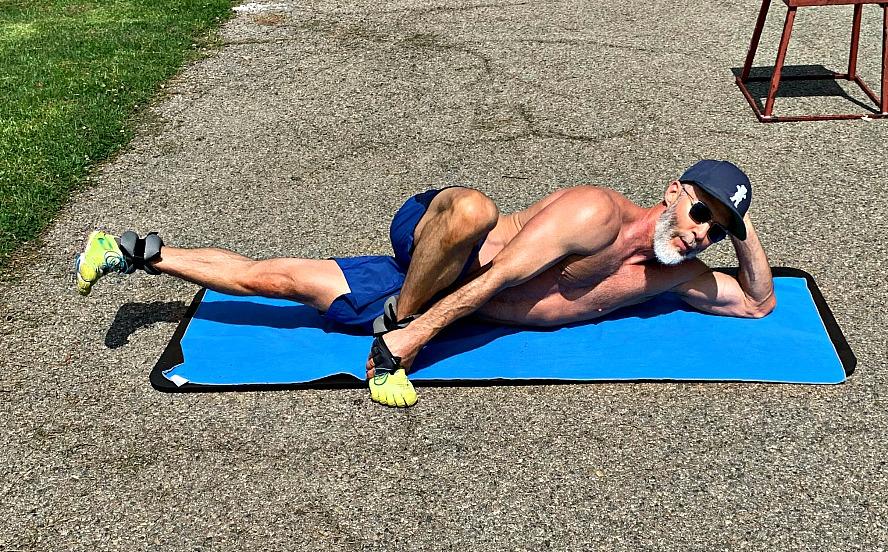 Older, fit man exercising in park.