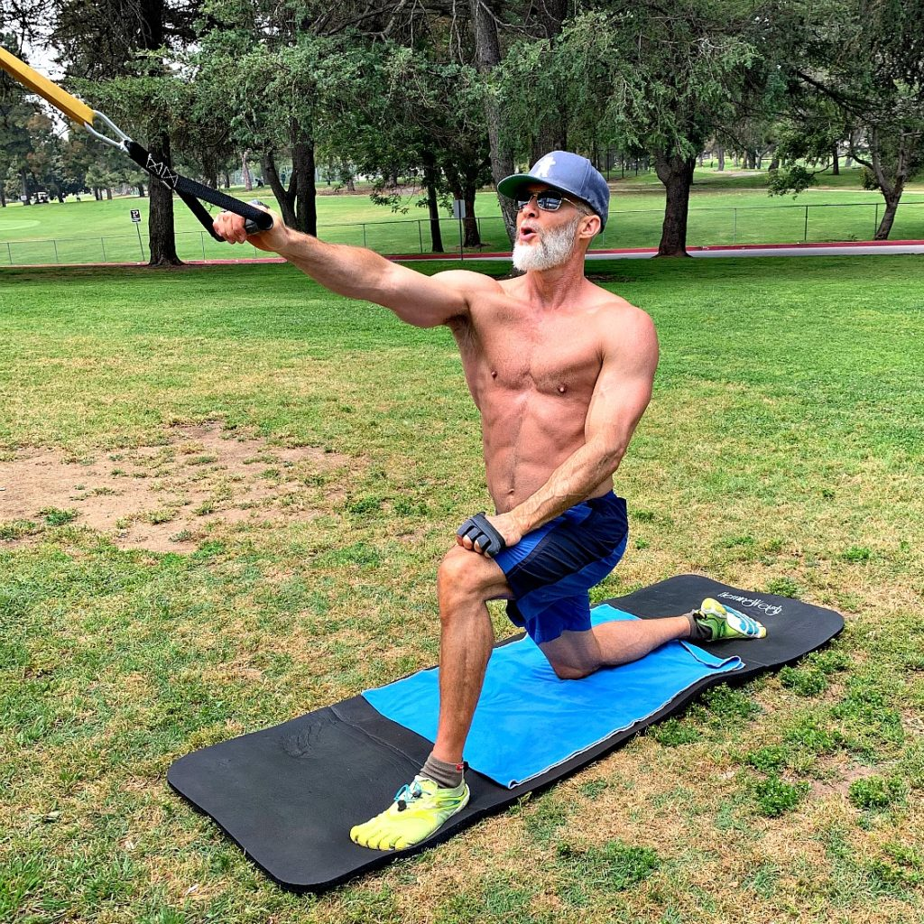 Older athlete using a resistance band to develop his back muscles.