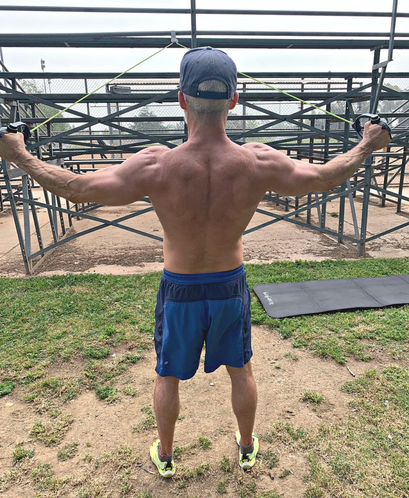Older athlete training upper body with resistance band at park.