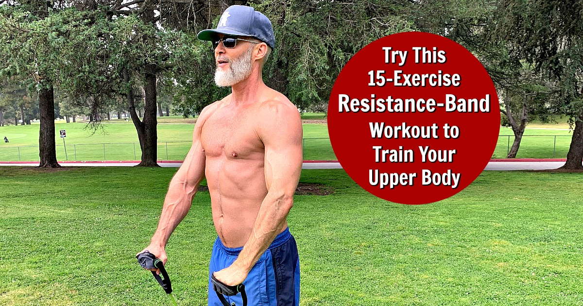 Older, muscled man works out in the park using a resistance band.
