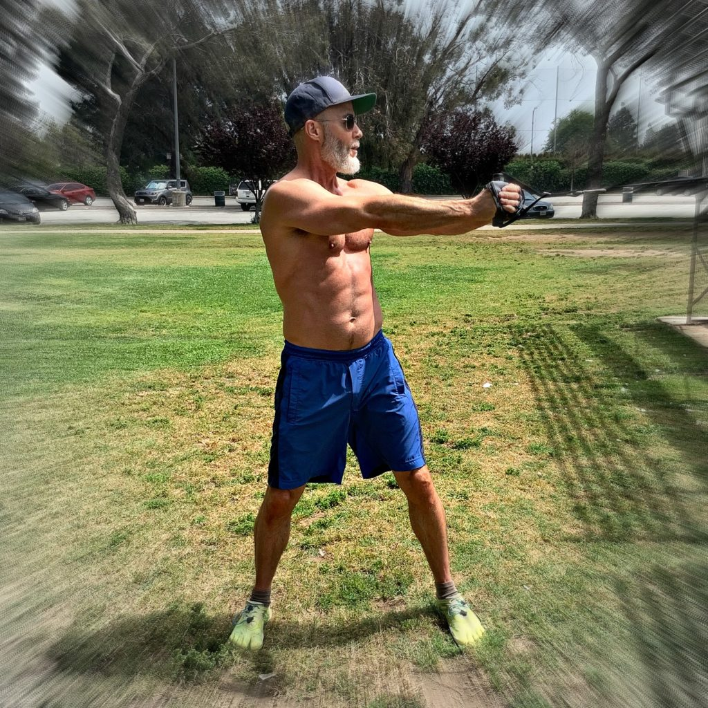 53 year-old athlete training in park with resistance bands.