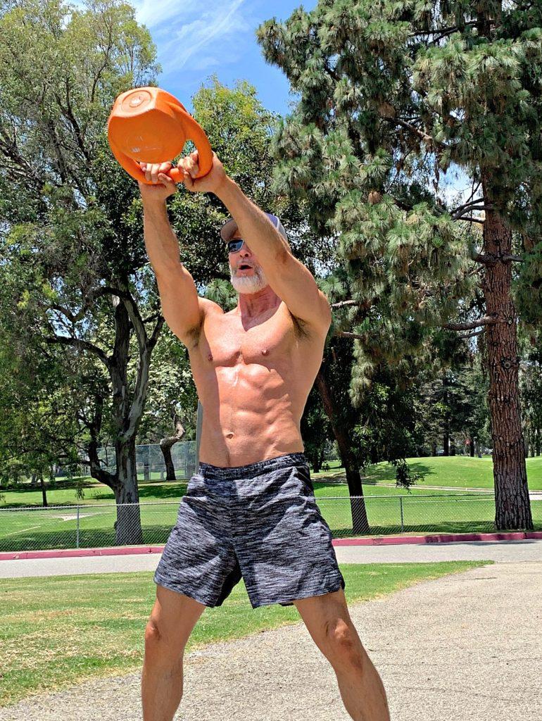 Dane Findley, Health Coach, demonstrates kettlebell swings outdoors.