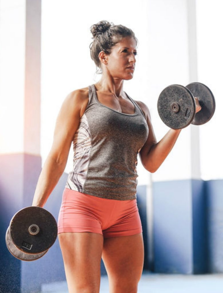 Mature women approach fitness with different priorities. This fit woman is sculpting her physique with dumbbells.