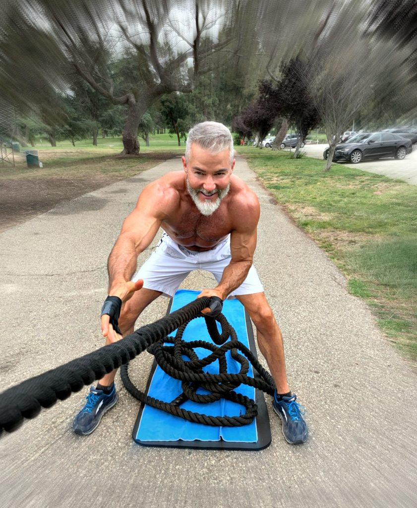 Muscled, older athlete demonstrates standing facing pulls with a battle rope, outdoors.