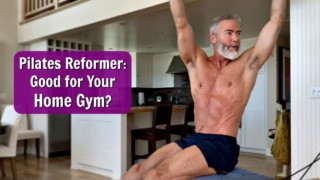 Mature male athlete training on a Pilates reformer in his home gym.