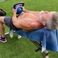 Mature male athlete does kettlebell pullover on an incline bench during Back Day.