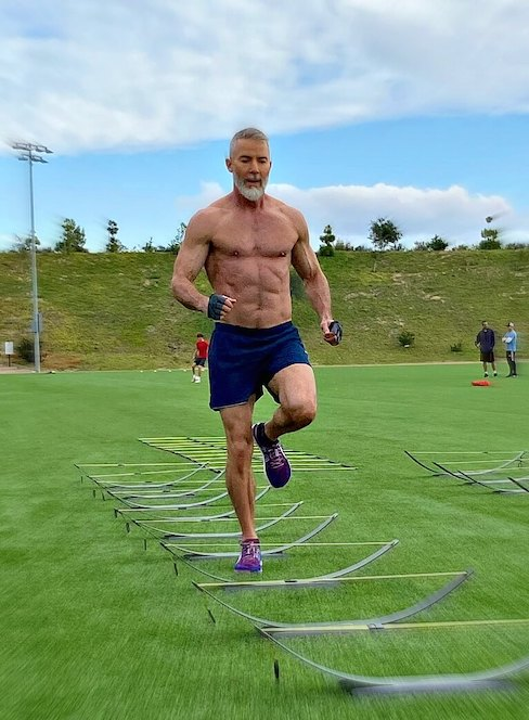 54 year-old athlete doing leg exercise drills at the park.