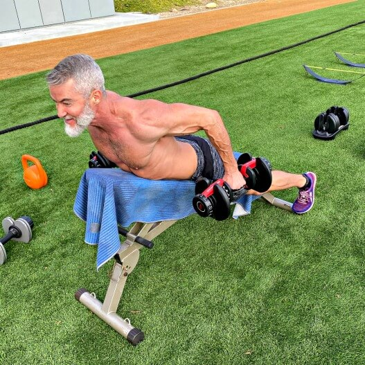 Older athlete improves posture by doing rear deltoid dumbbell fly exercise on back day.