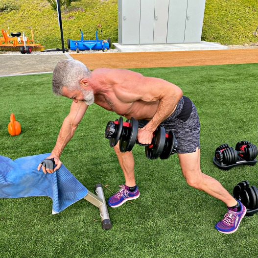 Silver-haired athlete does dumbbell rows to engage his back muscles.