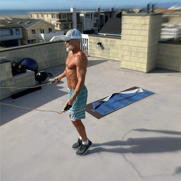 Mature athlete jumping rope during rooftop workout.