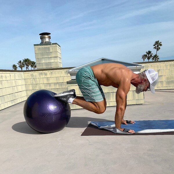 Senior male does core exercises with stability ball to warm up for a dumbbell workout.