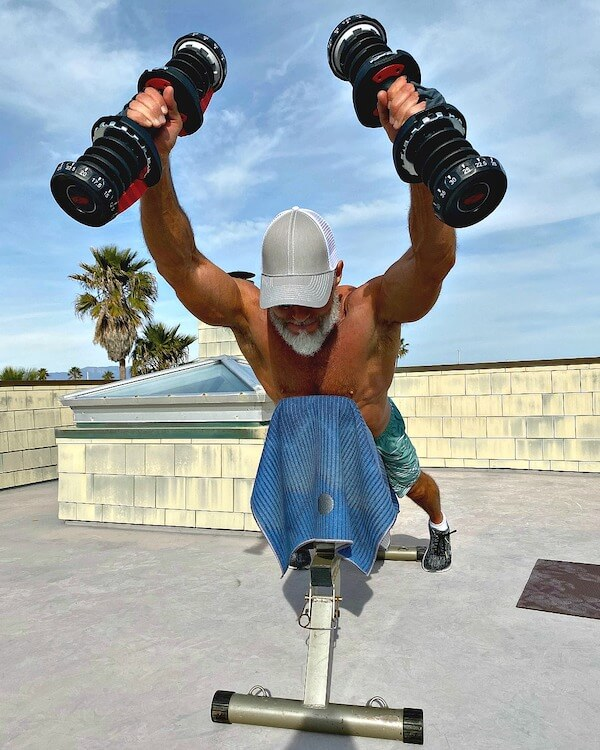 Athlete doing prone front arm raises with dumbbells to strengthen his posterior chain of muscles.