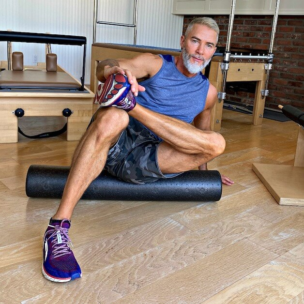 54-year old man warms up on foam roller before intense workout.