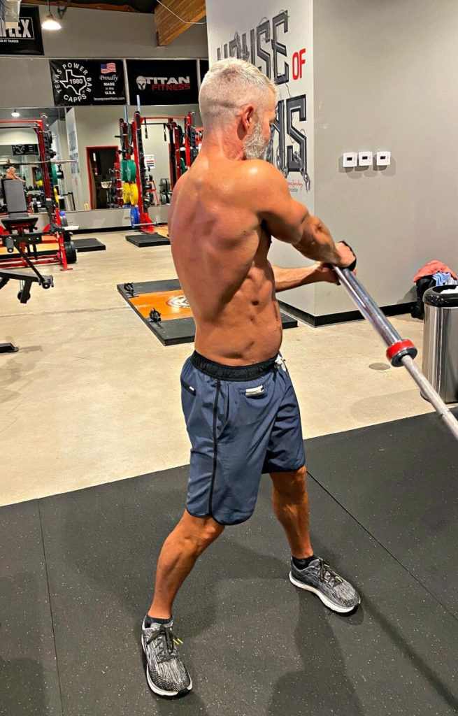 Man doing landmine rotational chops exercise with leaning barbell.