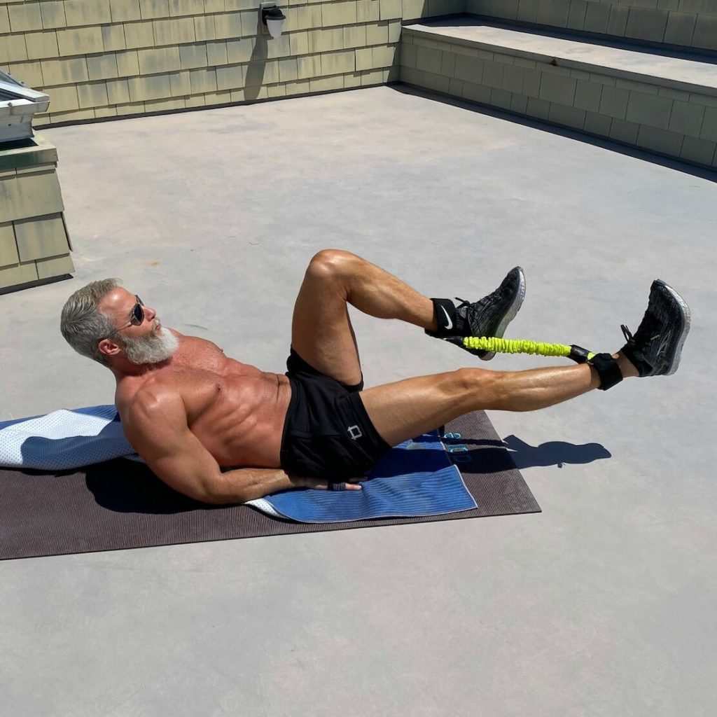 Dane Findley, age 54, does lower-body workout using resistance bands.
