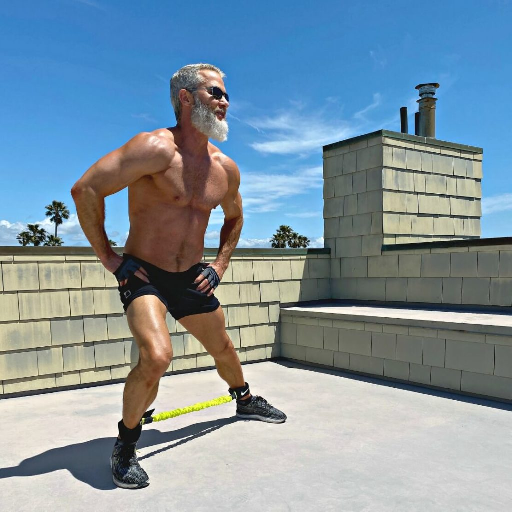 Dane Findley, age 54, trains his legs using resistance bands.