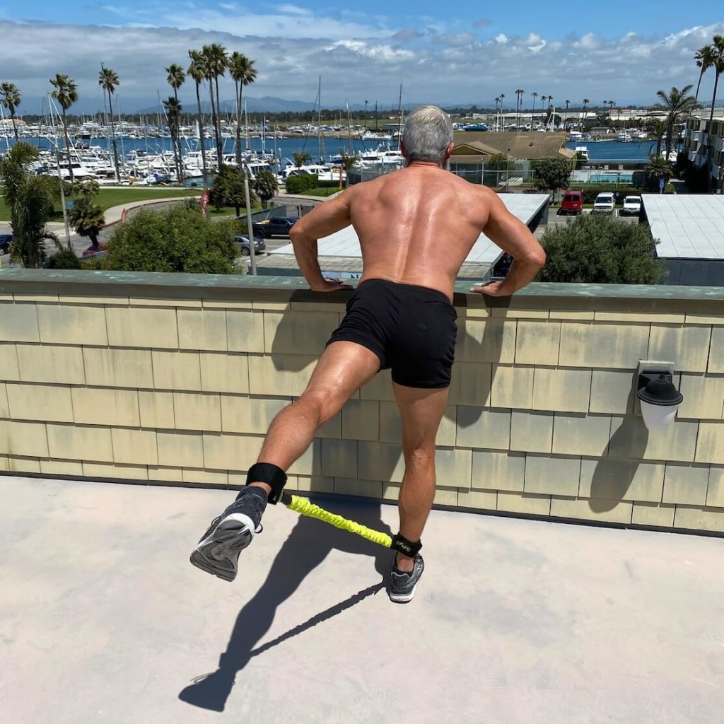 Mature athlete trains his glutes using resistance bands.