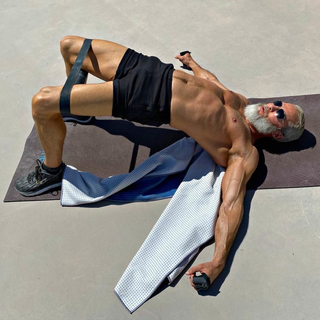Silver-bearded man does glute bridge exercise with resistance bands.