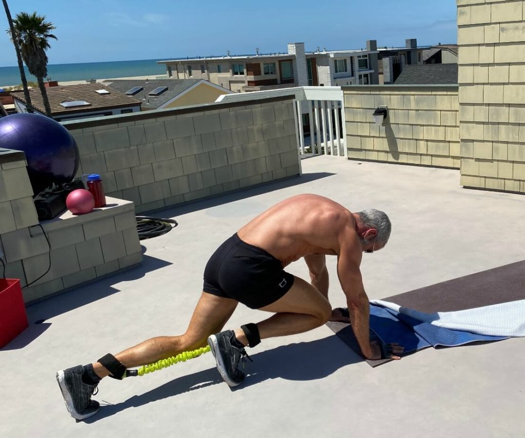 Older man does mountain climbers exercises with resistance bands.