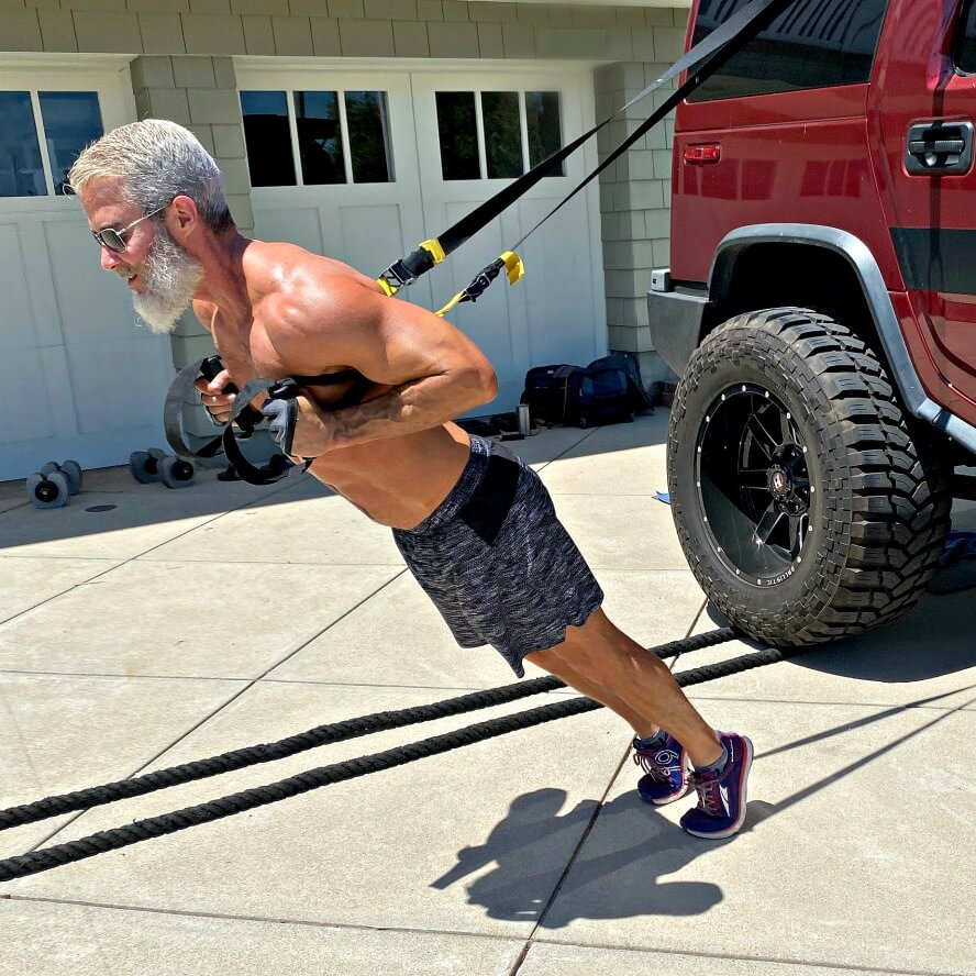 Training the suspended heel-raise exercise for calves in the driveway.