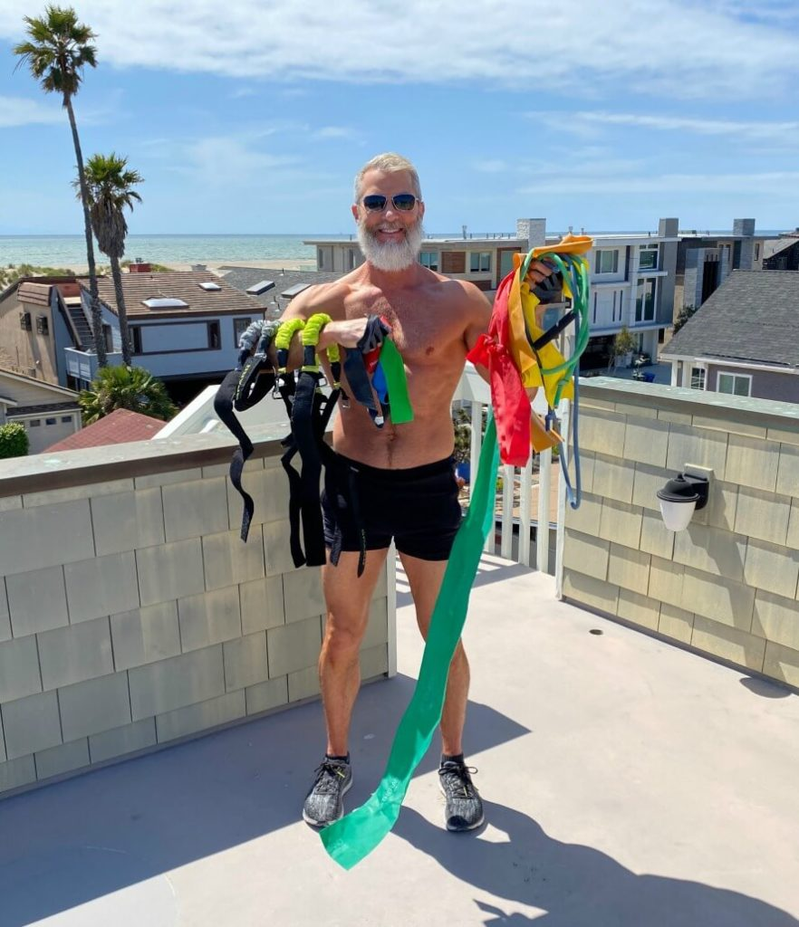 Mature athlete holding a variety of resistance bands in preparation for a lower body workout.