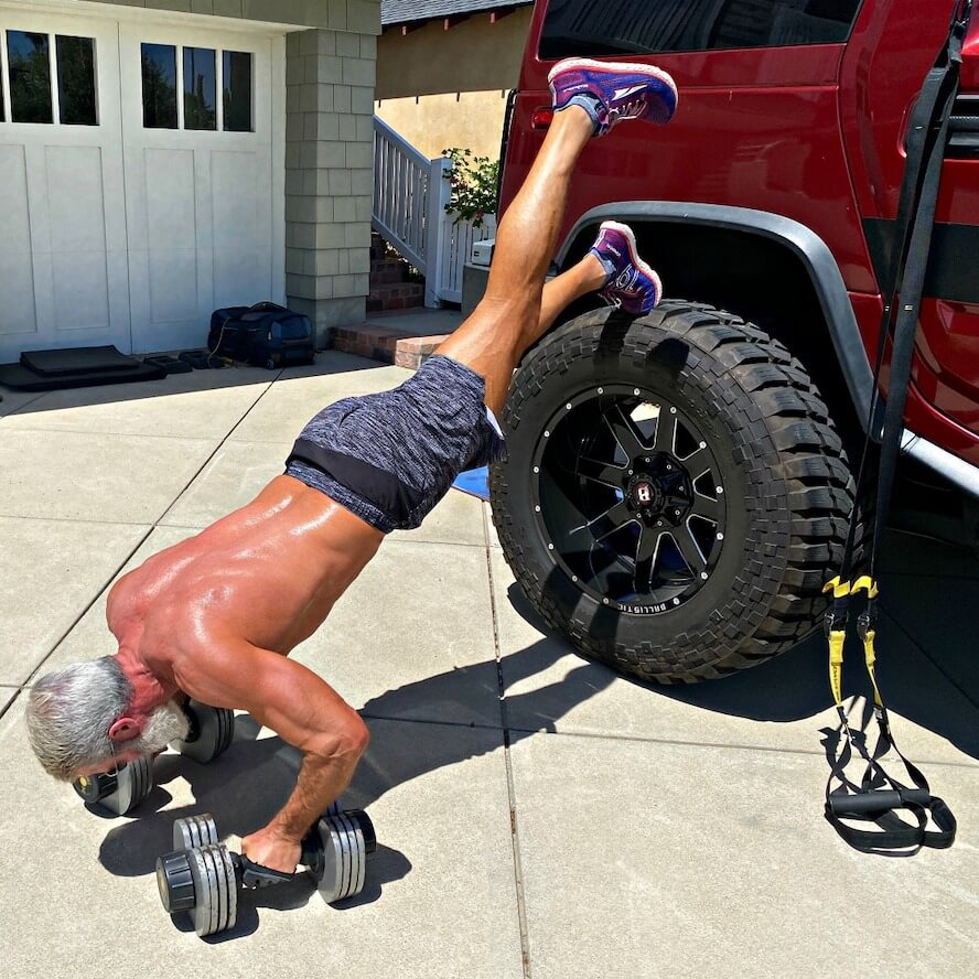 Mature athlete does driveway training workout, including decline push-ups.