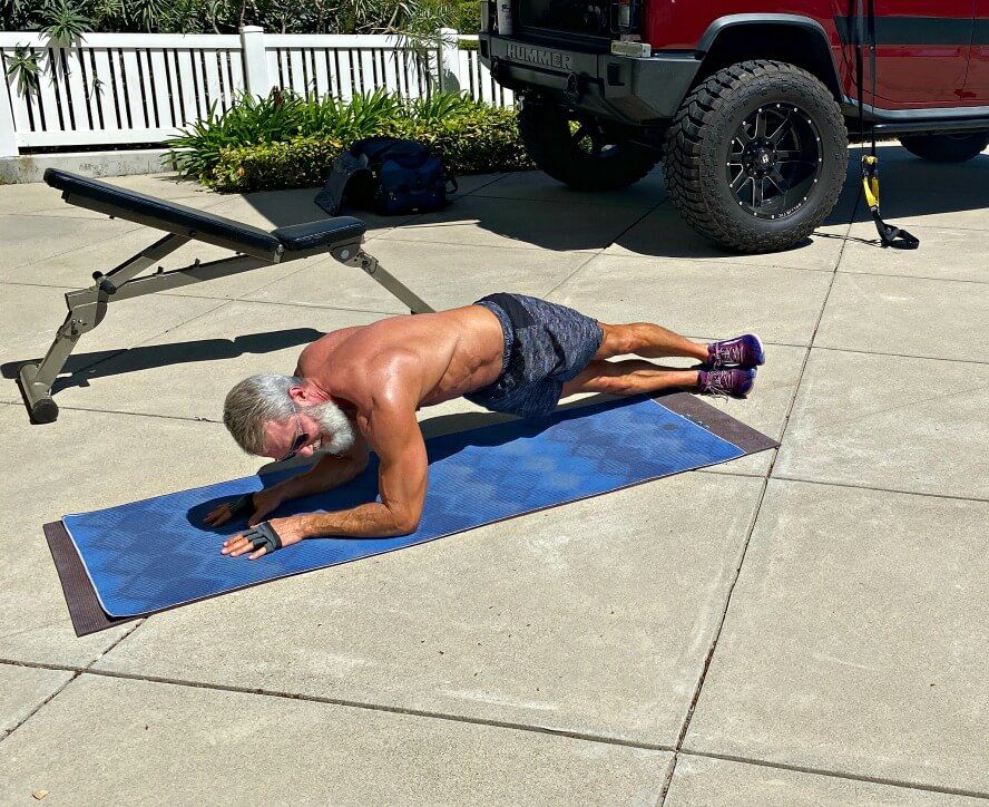 Man does abdominal training in the sun and fresh air of his driveway.
