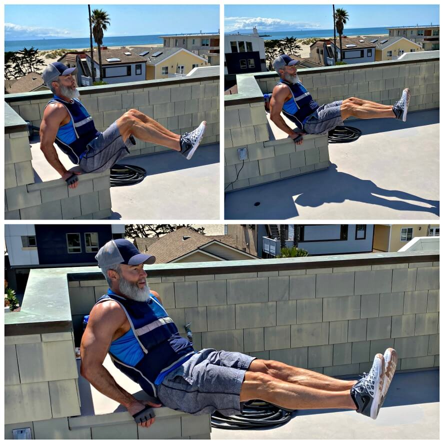 Man doing abdominal exercises outdoors while wearing a fitness vest.