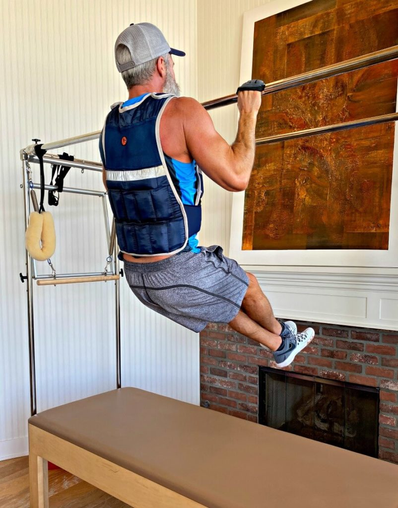 Man doing pull-ups exercise in weighted vest.