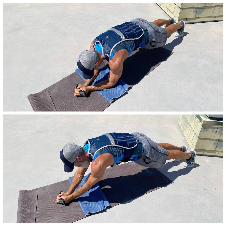 Exerciser trains his triceps and chest muscles while wearing a weighted vest.