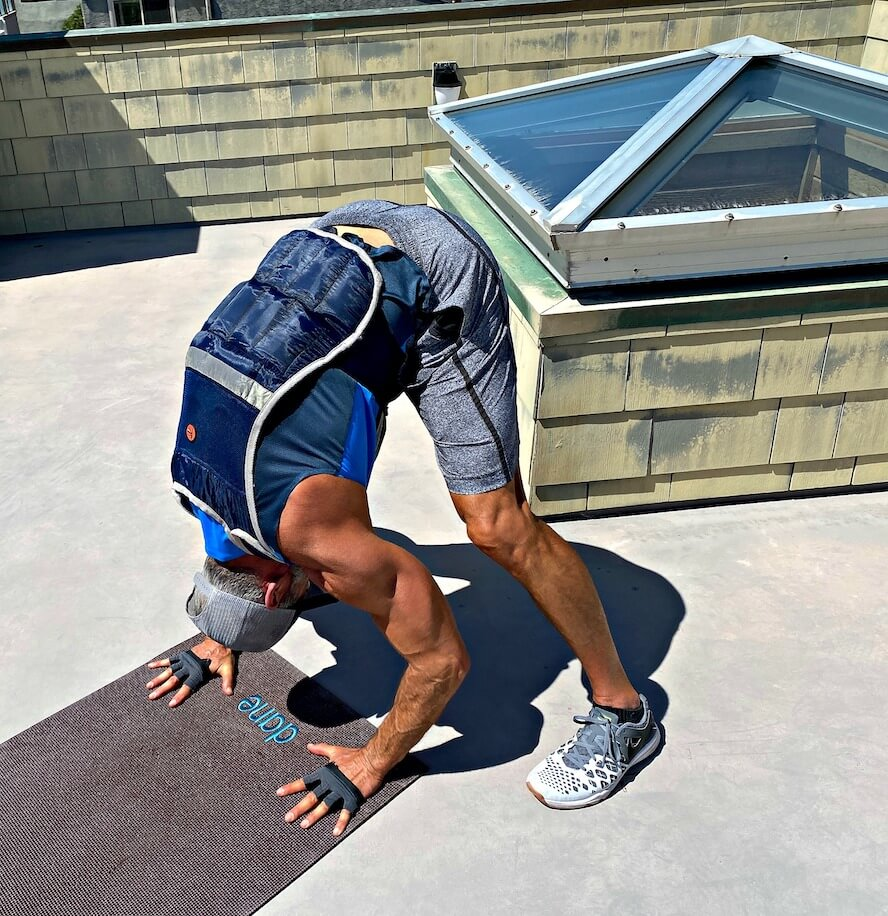 Dane Findley, age 54, does tricep bent-over handstand pushups while wearing a weighted vest.