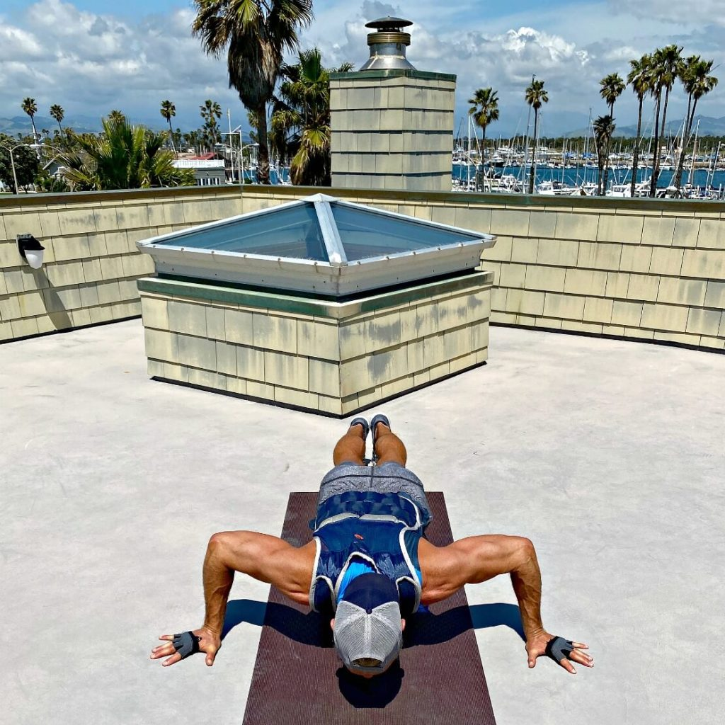Wide-stance push-ups in a fitness vest for creating sculpted arms and powerful chest.