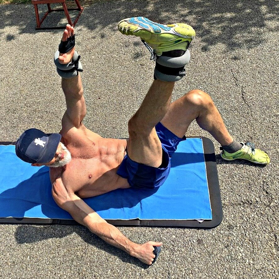 Mature athlete doing exercises with ankle weights, outdoors.