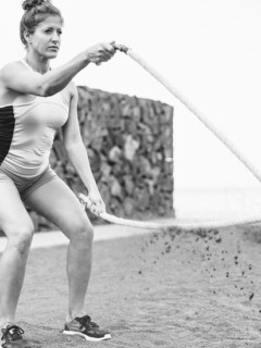 mature female athlete trains with battle rope
