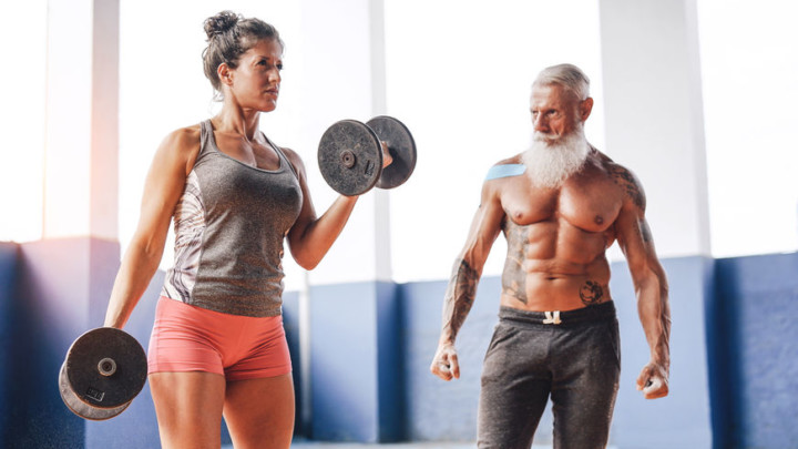 Mature, fit couple doing dumbbell workout.
