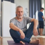 mature fit man preparing for mat workout