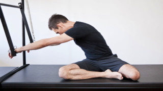 flexible, healthy man using trapeze table